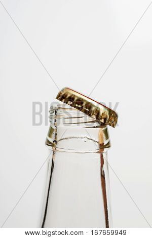 Transparent Glass Bottle Neck With Open Metal Lid On A White Background