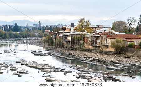 Old wrecked buildings of Kutaisi and the mountain river right in the city centre, Georgia