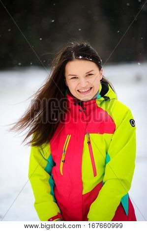 Lovely young woman brunette in a bright jacket on walk in winter day. It is snowing. The woman stands without headdress and joyfully laughs. Snowflakes lie on dark hair.