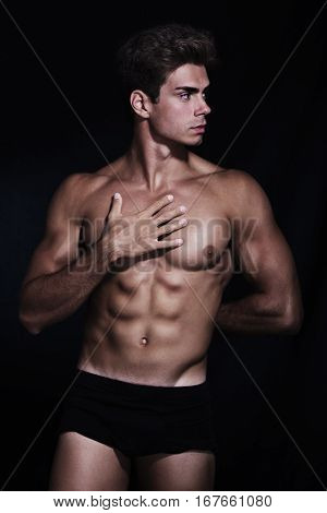 Italian model muscular man. Underwear portrait. A young Italian boy shirtless posing on a black background. Muscular and athletic. Well-defined muscles.