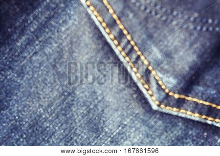 Blurred Close Up Picture Of Blue Jeans Fabric With Stitch.