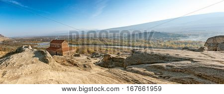 Panoramic view of the rock-hewn town of Uplistsikhe overlooking the distant city and river