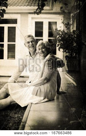 Grey background against portrait of senior couple sitting in yard