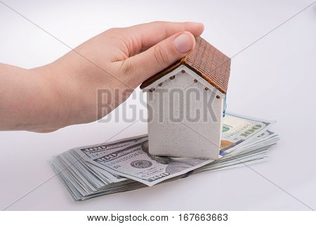 Hand Holding  A Model House By The Side Of Turkish Lira Banknotes