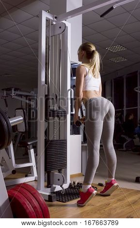 A young sporty girl in leggings with cool booty trains in the gym, good motivation
