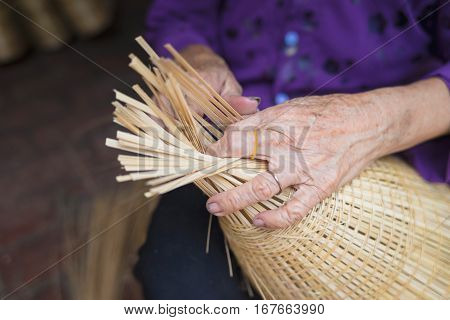 Woman Hand Weaving Tropical Bamboo Fish Trap In Traditional Crafts Village In Vietnam