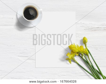 Spring styled stock photo. Feminine mock-up with daffodil flowers, Narcissus, list of paper, and cup of coffee. Shabby white background. Flat lay picture, top view. Image for blog or social media.