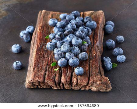 Wet blueberry on a wooden board