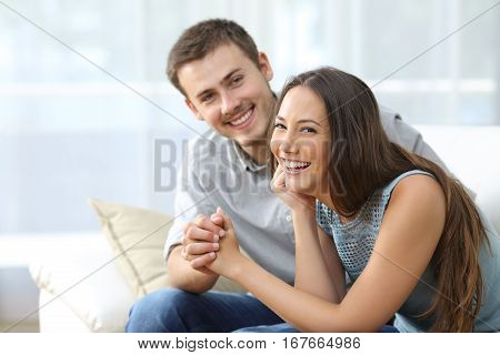 Happy marriage posing and looking at you sitting on a sofa in the living room at home