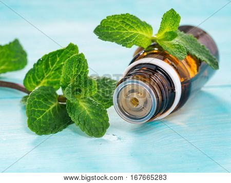 Essential oil of peppermint in a small brown bottle with fresh green mint on blue wooden background. Selective focus, shallow DOF. Copy space