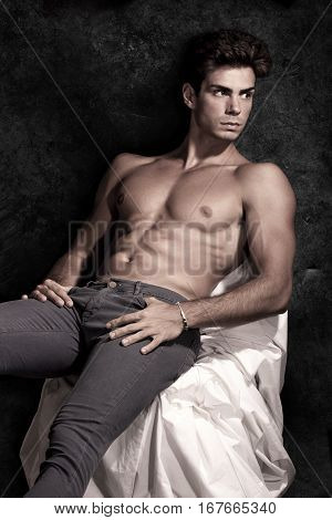 Italian model muscular man. Without t-shirt. A young Italian boy shirtless with jeans denim posing sitting on a grunge background. Muscular and athletic. Well-defined muscles.