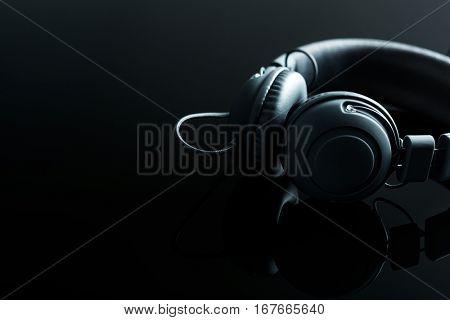 The vintage headphones on black table.