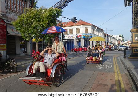 PENANG MALAYSIA- 29 DECEMBER 2016: Local citizen cycling his trishaw that serves as one of the popular modes of transport and also attractions in Penang