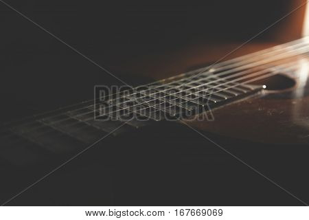Acoustic guitar against on the wooden background.