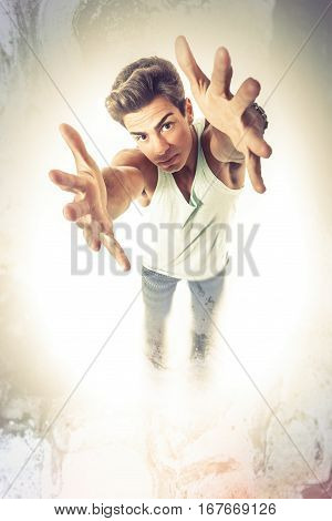 Man trying taking something with two hands, arms outstretched. A young man seen from above stretches out his arms to catch and grab something with two hands. Arms outstretched. Hairstyle.
