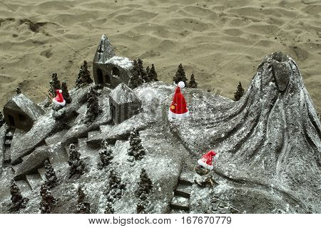 Beautiful sandcastle or sculpture miniature building with red santa hats on grey sandy beach surface outdoors on sand texture background