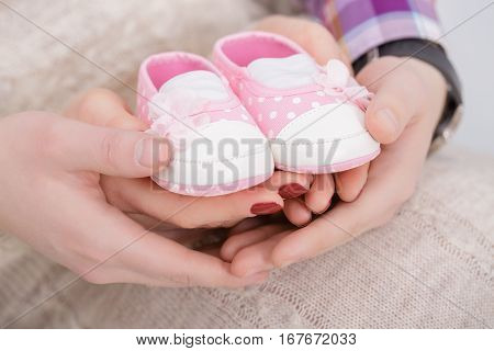pink booties for newborn baby in hands of mother and father. pregnancy
