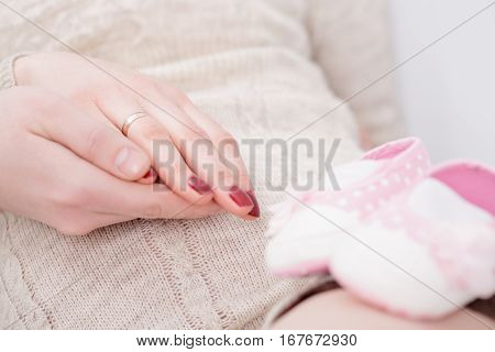 pregnancy - hands of mother and father.  pink booties for newborn baby in the foreground