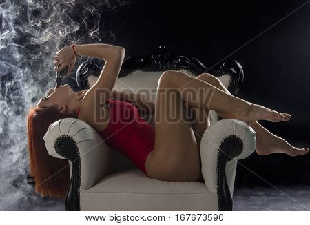 sexy woman smoking electronic cigarette and lying on the chair, vape mod concept