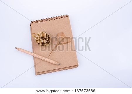 Heart Shaped Leaf,  Pine Cone And A Pencil On A Notebook