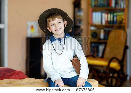 Portrait of little school kid boy wearing cowboy hat and playing at home. Smiling happy child having fun with dress up.