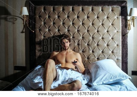 young handsome bearded man with bare muscular chest on sexy body in white bedsheet laying on bed in hotel bedroom with remote control and coffee cup
