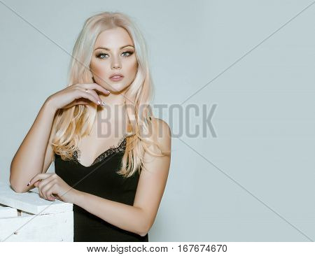 pretty girl or cute woman with long platinum blonde hair and fashionable makeup on face in sexy glamour black dress on grey background copy space