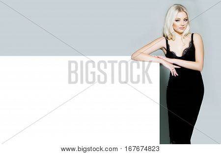 pretty girl or cute woman with long platinum blonde hair and fashionable makeup on face in sexy glamour black dress on white and grey background copy space