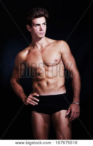 Great, muscular young man model in underwear. A muscular and handsome young man is posing in studio. He has a statuesque body and its appearance is truly beautiful. Trendy hairstyle. Wearing a black box underwear.