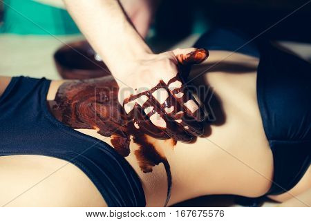 Female Sexy Belly And Male Hands On Chocolate Massage