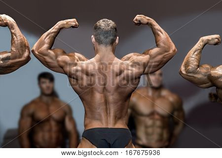 Bodybuilder flexing back and biceps. Muscular athlete posing on stage. Top sportsmen at bodybuilding competition. Opponents are watching.
