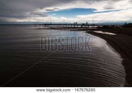 Issyk-Kul lake evening landscape. Water, gangway, blue sky and cloiuds, people silhouettes