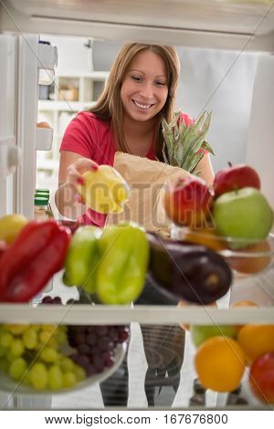 Young housewife put peppers from market in fridge