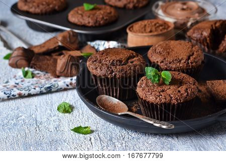 Chocolate muffins with nuts and peanut butter on a concrete background