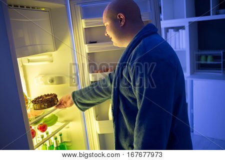 At night corpulent  guy take chocolate cake from refrigerator dangerous for obese