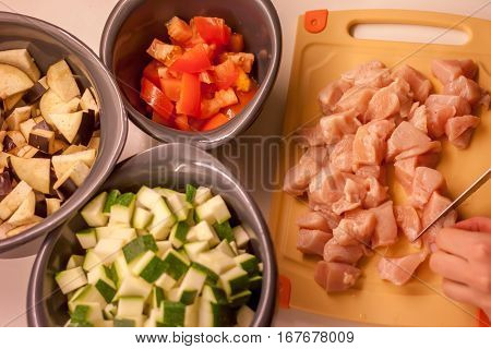 female hands cooking ragu of eggplant tomatoes zucchini and chicken