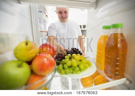 Man choose grapes from fridge like good choice for healthy life