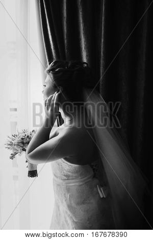 Bride Looks Thoughtful Through The Window During Preparations