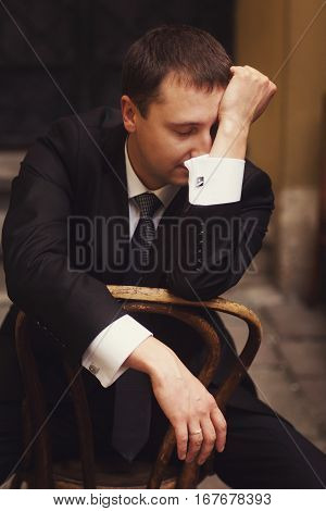 Man in a black suit looks tired sitting on a wooden chair on the street