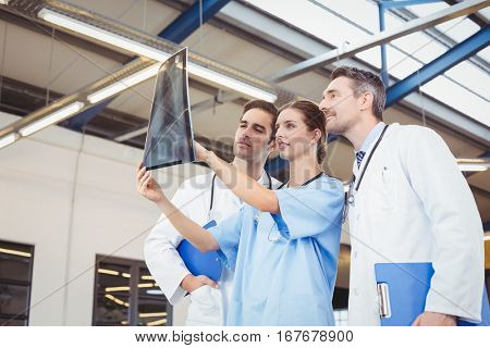 Concentrated doctors checking X-ray while standing at hospital