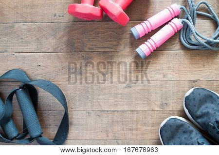 Flat lay of cellphone red dumbbells and sport equipment on wood background. Sport wear Sport fashion Sport accessories Sport equipment top view background. Sport wear Sport fashion Sport accessories Sport equipment top view