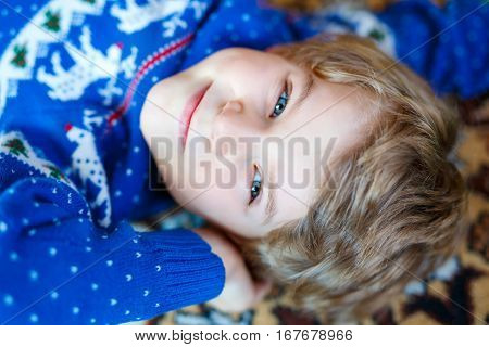 Portrait of beautiful little preschool kid boy. Smiling happy child looking at the camera. Boy wearing blue clothes with norvegian christmas pattern. Family, happiness, joy