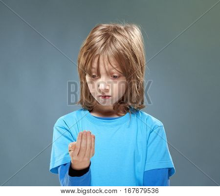 Boy in Blue Top Looking at his Hands