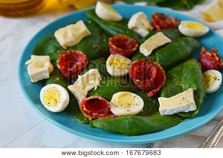 Salad with spinach brie cheese and quail eggs on a marble background