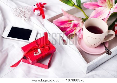 present box and smartphone, tray with cup of hot tea and flowers in the bed