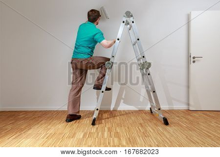 Man is painting a wall white.He stands on an a ladder.