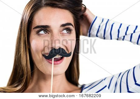 Smiling woman holding artificial mustache on white bckground