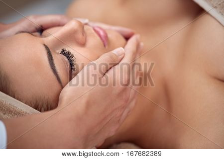 Close-up of a young woman getting spa treatment at beauty salon. spa face massage. facial beauty treatment. spa salon.