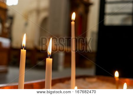Thin burning candles. Candles in church. Atmosphere of spirituality.