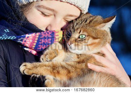 Outdoor portrait of a happy teen girl holding her red cat.Winter scene.